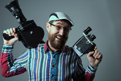 Laughing bearded man two old retro film camera Stock Image