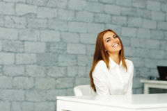 Laughing beautiful businesswoman sitting at the table Royalty Free Stock Photography