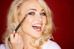 Laughing beautiful woman applying blusher Stock Photos