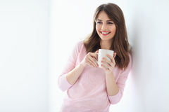Laughing beautiful woman with cup of coffee on white background. Copy space Stock Photos