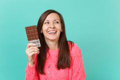 Laughing beautiful young girl in knitted pink sweater looking aside hold in hand chocolate bar isolated on blue