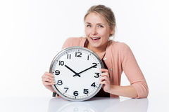 Laughing beautiful young woman displaying a clock Royalty Free Stock Photos