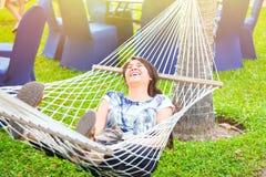 Laughing biracial teen girl relaxing in hammock Royalty Free Stock Image