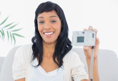 Laughing black haired woman in white clothes taking a picture of herself. In a living room Stock Image