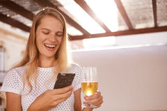 Laughing blond with beer and cellphone Stock Image