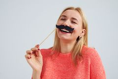 Laughing blond with fake moustache. Isolated on white Stock Photography