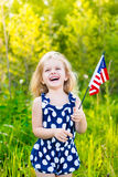Laughing blond little girl with curly hair holding american flag. Laughing blond little girl with long curly hair holding american flag, outdoor portrait on royalty free stock images