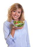 Laughing blond woman eating fresh salad Stock Photo
