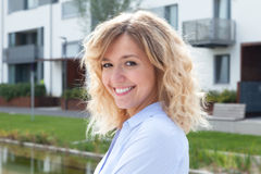 Laughing blond woman in front of her new apartment. Attractive laughing woman with curly blond hair outside in front of her new apartment Royalty Free Stock Images
