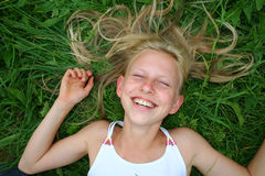 Laughing blonde. Young blonde girl laughing in grass Stock Photography