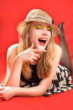 Laughing blonde in beach hat. Lying with eyes closed royalty free stock image