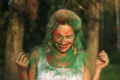 Laughing blonde girl wearing white shirt and posing covered with dry paint at the Holi Festival. Laughing blonde woman wearing white shirt and posing covered royalty free stock image