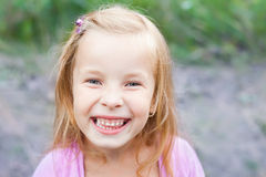 Laughing blonde little girl outdoors Royalty Free Stock Image