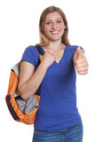 Laughing blonde student with backpack showing thumb up Stock Photo