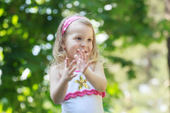 Laughing blonde toddler girl clapping with her Royalty Free Stock Image