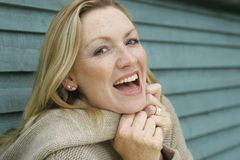 Laughing Blonde Woman. A young blond woman wrapped up warm outside laughing Royalty Free Stock Photo