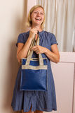 Laughing Blonde Woman With Blue Leather Purse Royalty Free Stock Photography