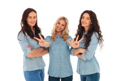 Laughing blonde woman making the victory sign near friends Royalty Free Stock Photography