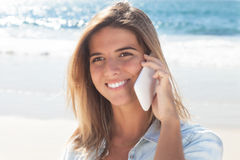 Laughing blonde woman with mobile phone at beach Stock Image