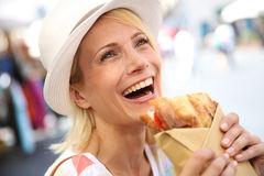 Laughing blonde woman savouring Focaccia sandwich Stock Photo
