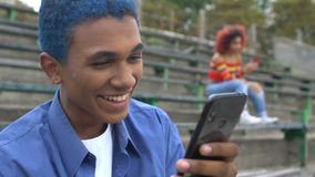 Laughing blue-haired male student watching funny video on smartphone, app. Stock footage stock video footage