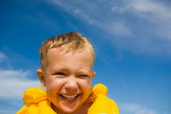 Laughing boy. The laughing boy in a life jacket on a beach Stock Image