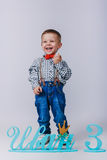 Laughing boy in blue jeans with braces on grey background Royalty Free Stock Images