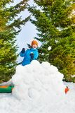 Laughing boy in blue winter jacket plays snowballs Royalty Free Stock Image