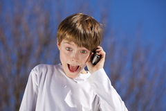 Laughing boy with cell phone. A laughing 9 years old boy phoning with a cell phone Royalty Free Stock Photography