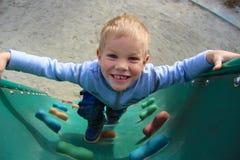 Laughing boy climbing Stock Photos