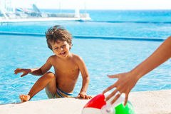 Laughing boy climbs up on boarder of pool to ball. Laughing boy climbs up on stone boarder of swimming pool and looks at adult hand and ball on beautiful ocean Stock Photography