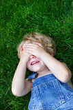 Laughing boy covering his eyes Stock Photo