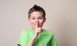 Laughing boy doing a silence gesture. Kid putting finger up to l stock photos