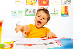 Laughing boy drawing with pencil on the paper. And pointing with finger while sitting at the table with drawings on background Stock Image