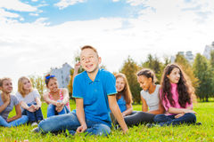 Laughing boy and friends sitting together in park. Laughing boy and friends sitting together on green meadow during wonderful sunny autumn day Royalty Free Stock Photos