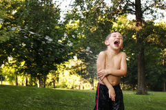Laughing boy getting sprayed with water royalty free stock photo