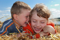 Laughing Boy and girl outdoors. Laughing Boy and girl laying on the straw outdoors over blue sky Royalty Free Stock Images