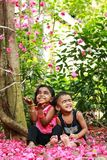 Laughing Boy and Girl Sitting on Pink Flower Petals Near Tree