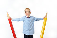 Laughing boy in glasses and bowtie posing with a huge pencils. Educational concept. Isolated over white. School preschool Stock Images