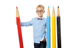 Laughing boy in glasses and bowtie posing with a huge pencils. Educational concept. Isolated over white. School preschool Royalty Free Stock Image