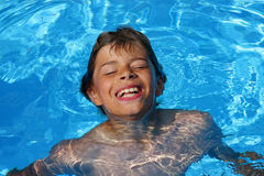 Laughing boy having fun in swimming pool Stock Image