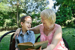 Laughing boy and his grandmother reading a book in the park Stock Images