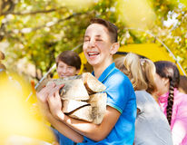 Laughing boy holding kindling wood on campsite Royalty Free Stock Photos