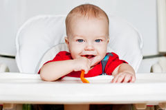 Laughing boy holding a spoon. On a white background stock photography