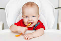 Laughing boy holding a spoon Royalty Free Stock Photo
