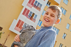 Laughing boy that holds rabbit in hands. Portrait of laughing boy that holds rabbit in hands stock photos