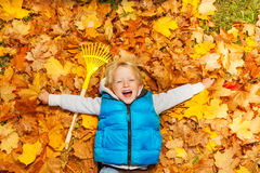 Laughing boy laying on the autumn leaves with rake Royalty Free Stock Images