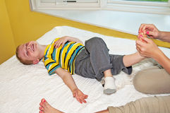 Laughing boy laying down foot tickled Royalty Free Stock Photos