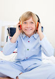 Laughing boy listening music sitting on bed Royalty Free Stock Photos