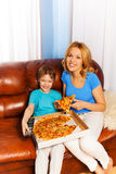 Laughing boy and mother eating pizza on the sofa Royalty Free Stock Photo